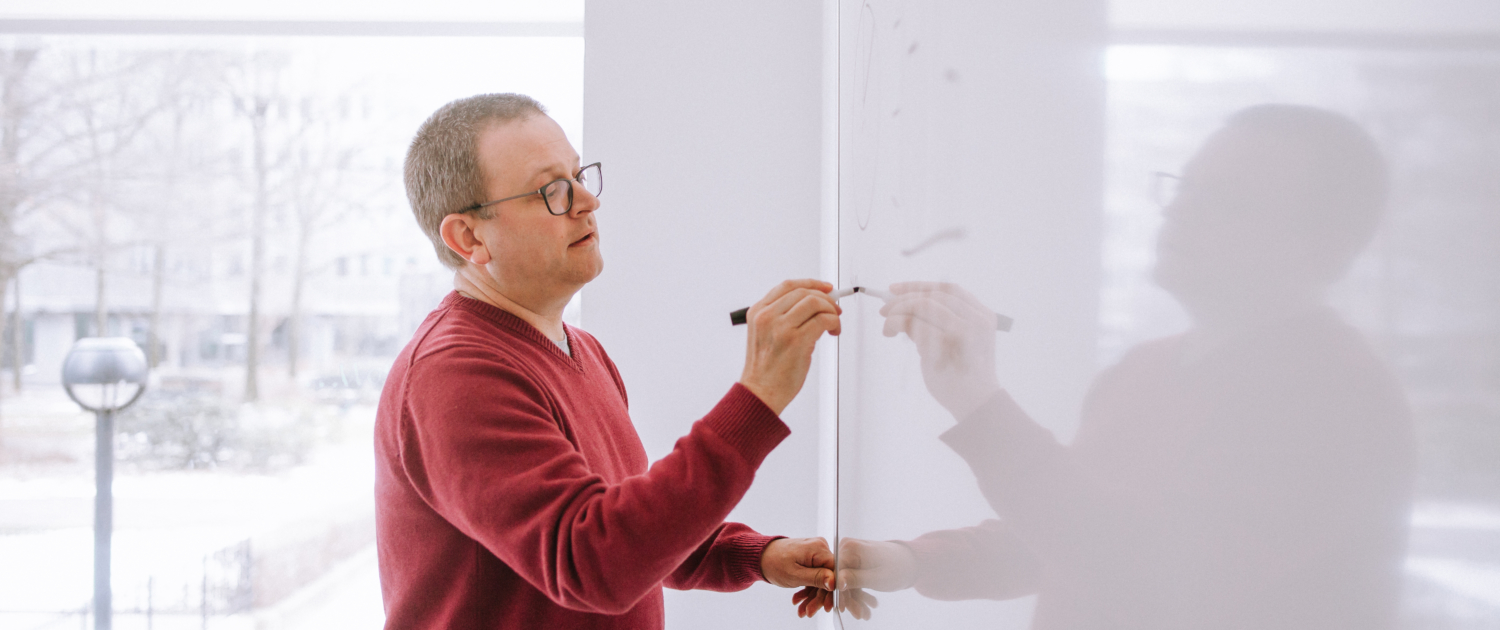 Flying Cork employee Tom Estlack drawing on a whiteboard to map out content and digital strategy in Pittsburgh